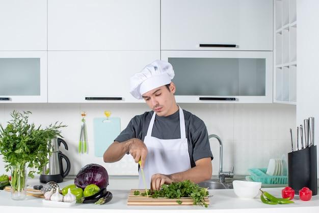 Vue de face jeune chef en uniforme coupant les verts sur la table