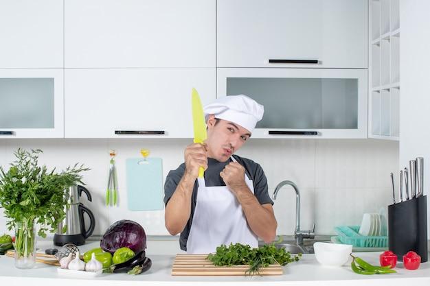 Vue de face jeune chef en uniforme montrant un couteau