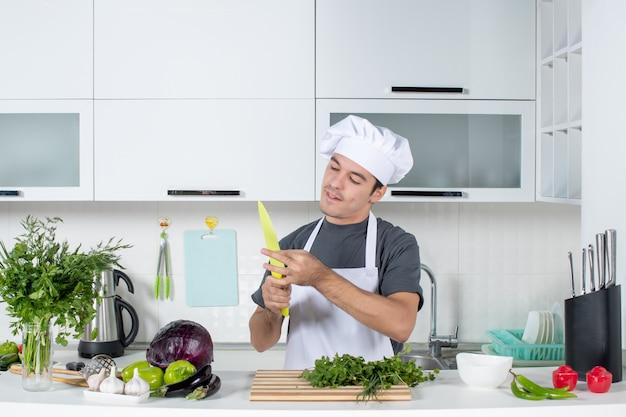 Vue de face jeune chef en uniforme nettoyant son couteau