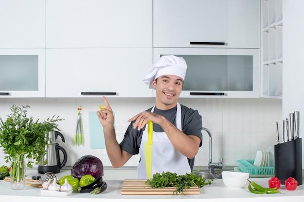 Vue de face jeune chef en uniforme pointant vers le plafond dans une cuisine moderne