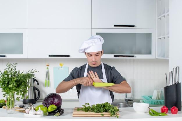 Vue de face jeune chef en uniforme regardant un couteau
