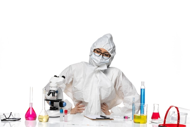 Vue de face jeune chimiste en combinaison de protection spéciale assis avec table pleine de solutions sur fond blanc virus laboratoire covid- chimie