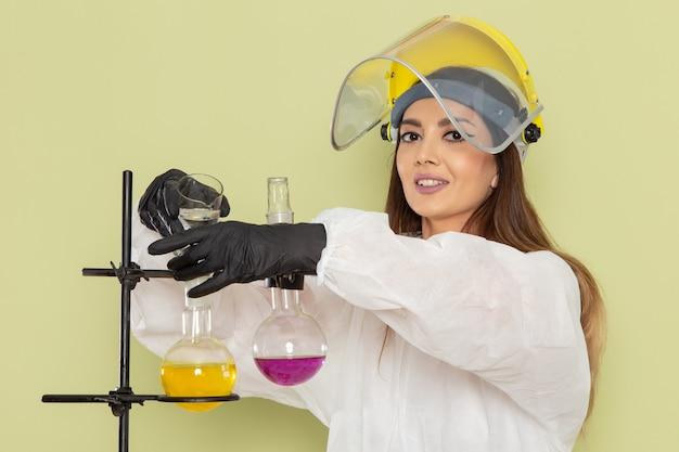 Vue de face jeune chimiste en combinaison de protection spéciale travaillant avec des solutions sur le mur vert chimie laboratoire chimie travail femelle science