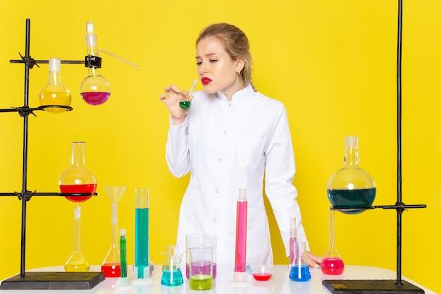Vue de face jeune chimiste en costume blanc en face de la table avec des solutions ed tenant un sur l'expérience scientifique de chimie de l'espace jaune