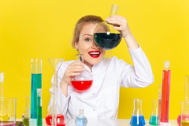 Vue de face jeune chimiste en costume blanc tenant différentes solutions sur la chimie de l'espace jaune