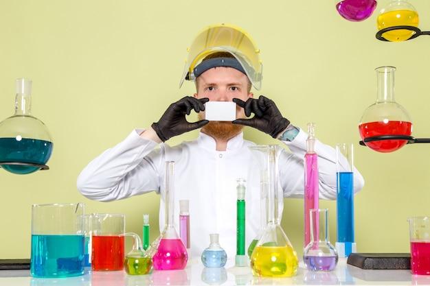 Vue de face jeune chimiste couvrant sa bouche avec une carte blanche