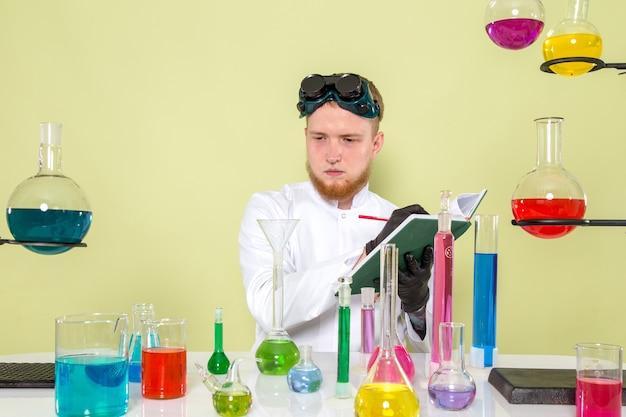 Vue de face jeune chimiste en prenant quelques notes sur les produits chimiques