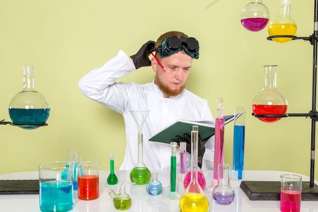Vue de face, jeune chimiste se gratte la tête
