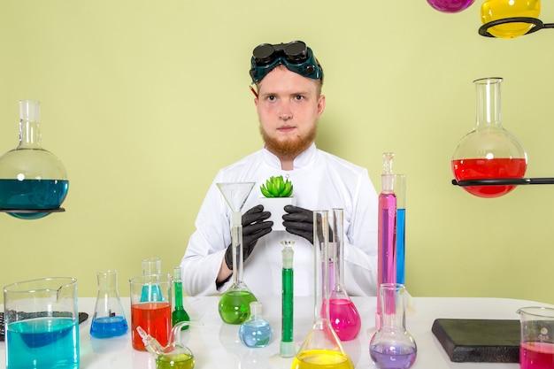 Vue de face jeune chimiste tenant sa plante fraîche dans un laboratoire
