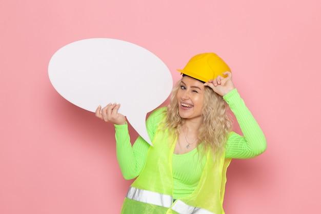 Vue de face jeune constructeur féminin en costume de construction verte casque tenant un grand panneau blanc tout en clignotant sur les travaux de construction de l'architecture de l'espace rose