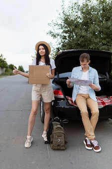 Vue de face jeune couple auto-stop randonnée en vacances