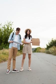 Vue de face jeune couple auto-stop randonnée