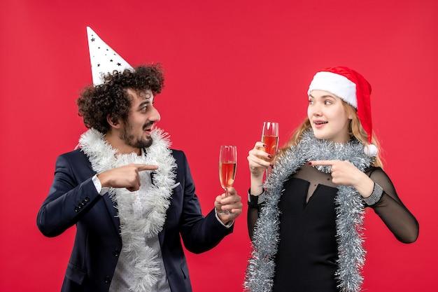 Vue de face jeune couple célébrant joyeusement le nouvel an sur le bureau rouge