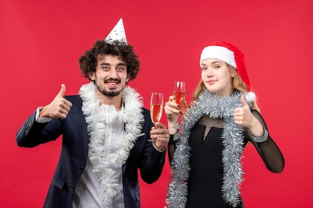 Vue de face jeune couple célébrant joyeusement le nouvel an sur le mur rouge
