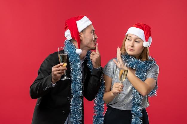 Vue de face jeune couple célébrant le nouvel an sur le bureau rouge aime la couleur de noël