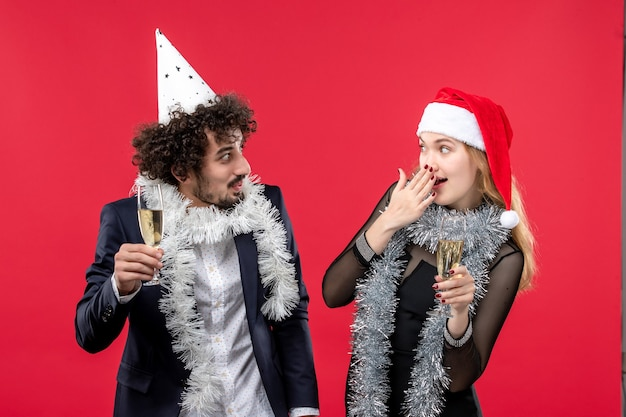 Vue de face jeune couple célébrant le nouvel an sur le bureau rouge vacances amour fête de noël