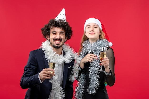 Vue de face jeune couple célébrant le nouvel an sur le bureau rouge vacances noël amour