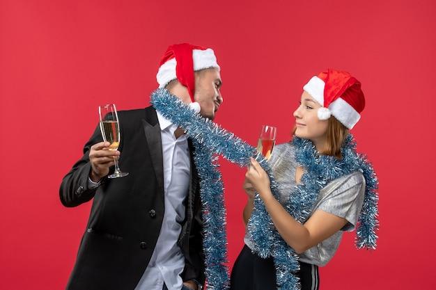 Vue de face jeune couple célébrant le nouvel an sur un mur rouge aime la couleur de noël