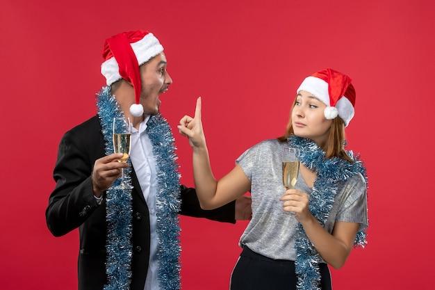 Vue de face jeune couple célébrant le nouvel an sur le mur rouge aiment les couleurs de noël