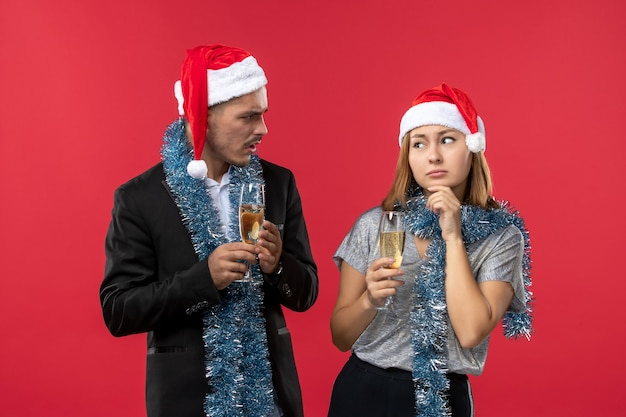 Vue de face jeune couple célébrant le nouvel an sur le mur rouge aiment les vacances de couleur de noël