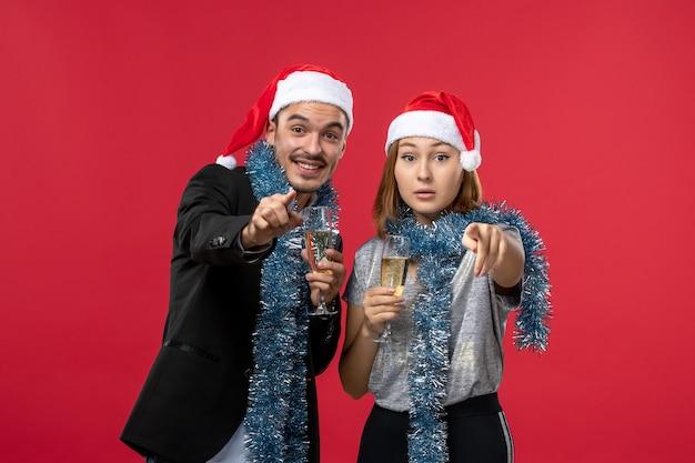 Vue de face jeune couple célébrant le nouvel an sur un mur rouge amour vacances couleur de noël