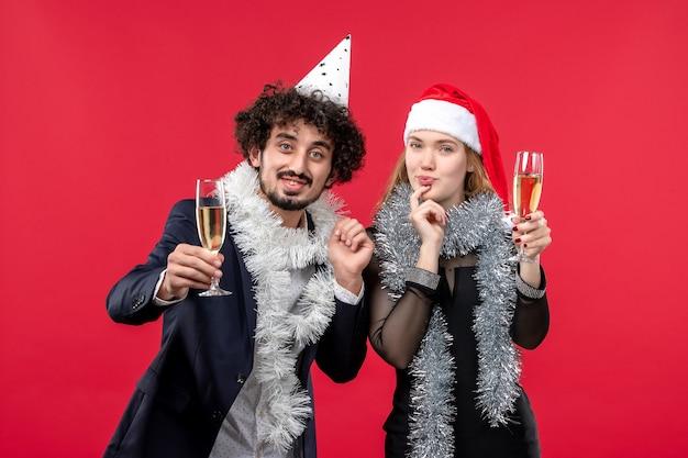 Vue de face jeune couple célébrant le nouvel an sur le mur rouge fête d'amour de noël