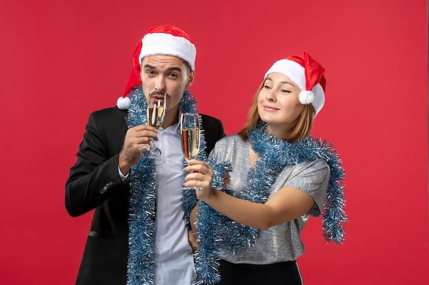 Vue de face jeune couple célébrant le nouvel an sur le plancher rouge love party noël