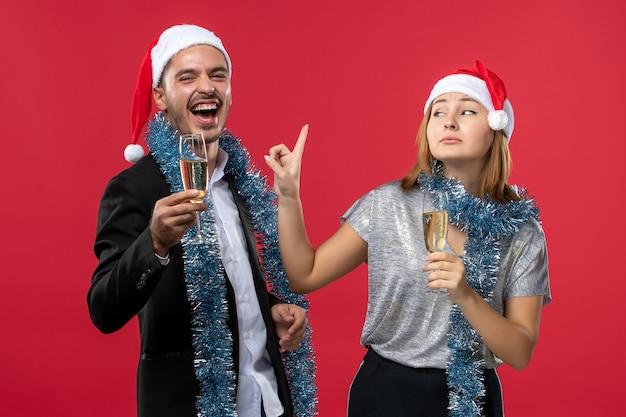 Vue de face jeune couple célébrant le nouvel an sur le sol rouge aime la couleur de noël