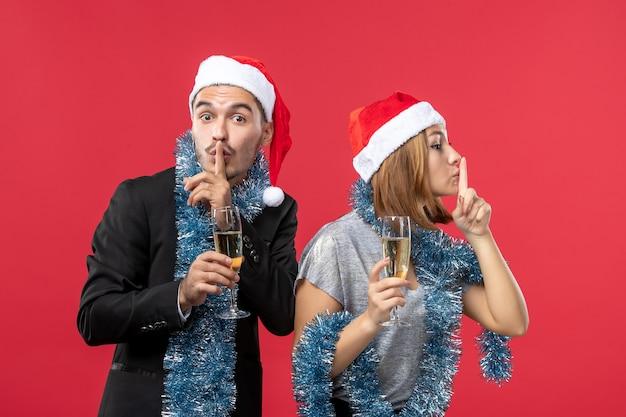 Vue de face jeune couple heureux célébrant le nouvel an sur le plancher rouge fête l'amour de noël