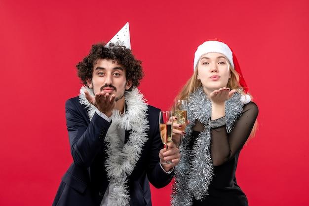 Vue de face jeune couple juste célébrer le nouvel an sur le mur rouge fête d'amour de noël