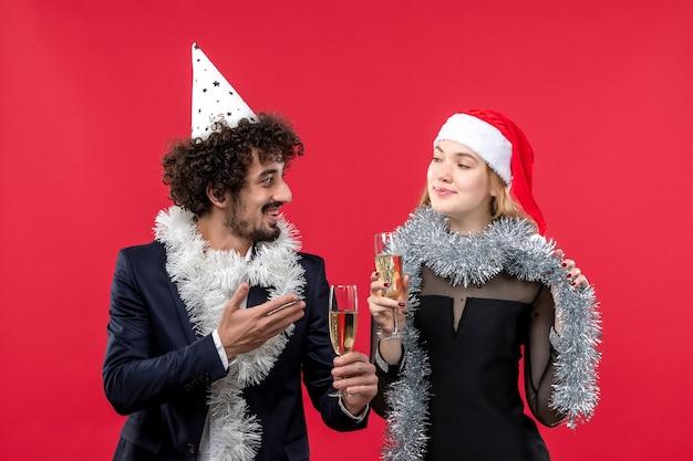 Vue de face jeune couple juste célébrer le nouvel an sur le mur rouge fête noël amour