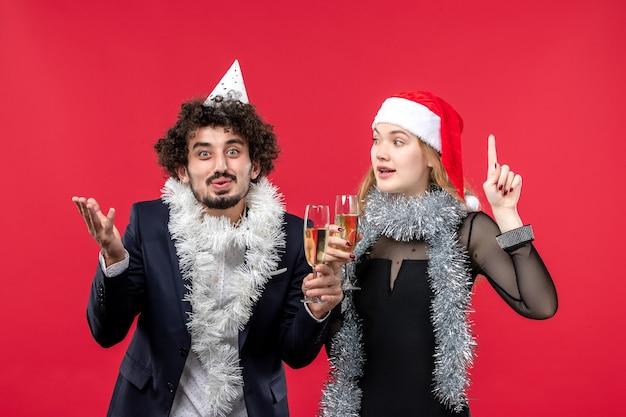 Vue de face jeune couple juste célébrer le nouvel an sur le mur rouge photo amour de noël