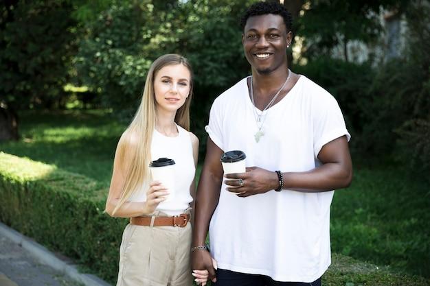 Vue de face, jeune, couple multiculturel, tenant mains