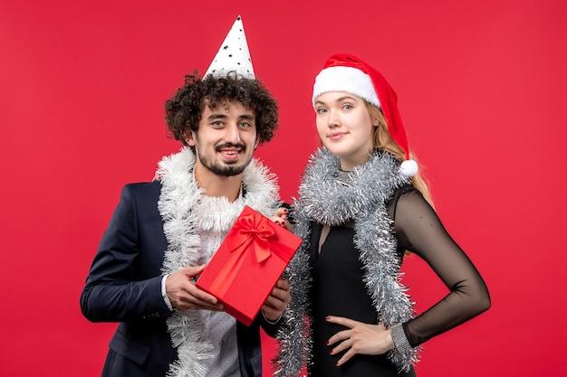 Vue de face jeune couple avec présent célébrant sur le mur rouge fête d'amour de noël