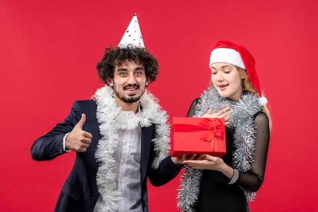Vue de face jeune couple avec présent célébrant sur le mur rouge fête noël amour