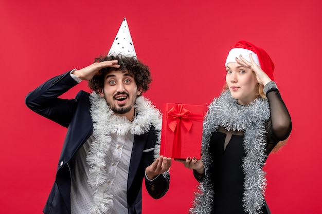 Vue de face jeune couple tenant le nouvel an présent sur les émotions de mur rouge noël amour
