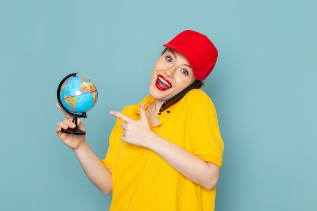 Vue de face jeune courrier en chemise jaune et cape rouge parlant au téléphone en souriant sur l'espace bleu