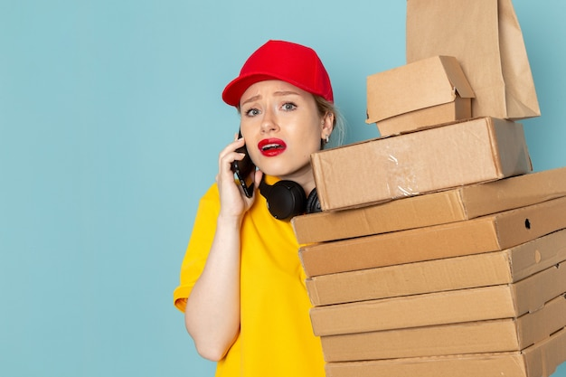 Vue de face jeune courrier en chemise jaune et cape rouge tenant multiplier les paquets sur le travail de l'espace bleu
