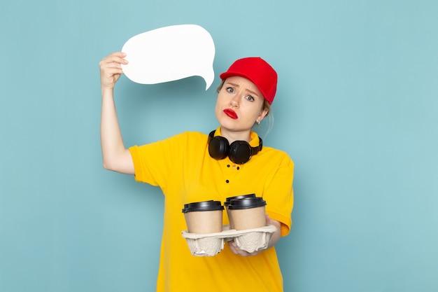 Vue de face jeune courrier en chemise jaune et cape rouge tenant des tasses à café panneau blanc sur l'espace bleu
