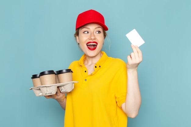 Vue de face jeune courrier en chemise jaune et cape rouge tenant des tasses à café en plastique carte blanche sur l'espace bleu