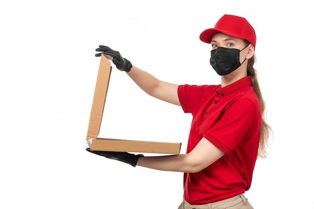 Une vue de face jeune courrier en chemise rouge bonnet rouge gants noirs et masque noir tenant une boîte à pizza vide sur le fond blanc offrant un uniforme de service