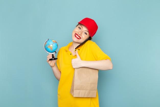 Vue de face jeune courrier féminin en chemise jaune et cape rouge tenant le globe parler au téléphone en souriant sur l'espace bleu
