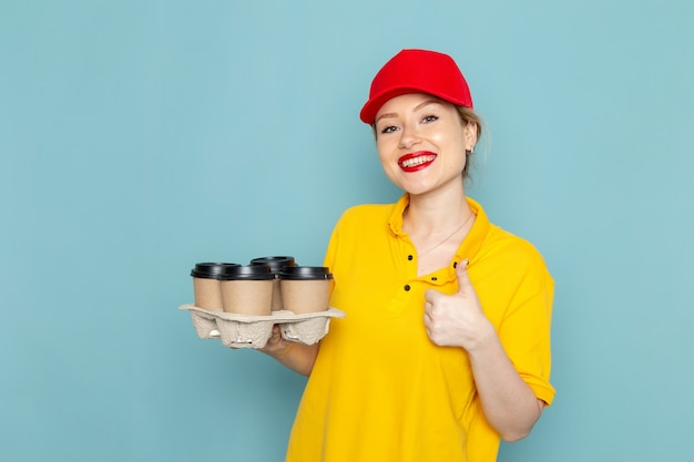 Vue de face jeune courrier féminin en chemise jaune et cape rouge tenant des tasses à café en plastique souriant sur l'espace bleu