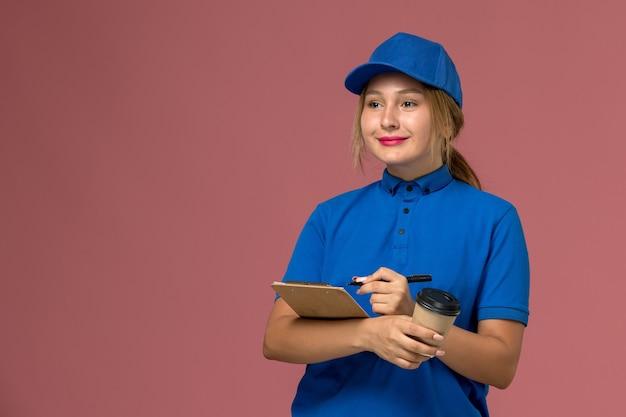 Vue de face jeune courrier féminin en uniforme bleu posant tenant une tasse de café et bloc-notes avec un léger sourire, femme de livraison uniforme de service