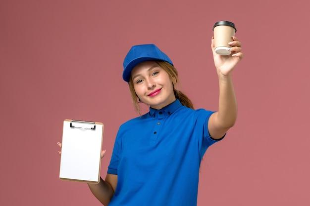 Vue de face jeune courrier féminin en uniforme bleu posant tenant une tasse de café et bloc-notes avec sourire, femme de livraison uniforme de service