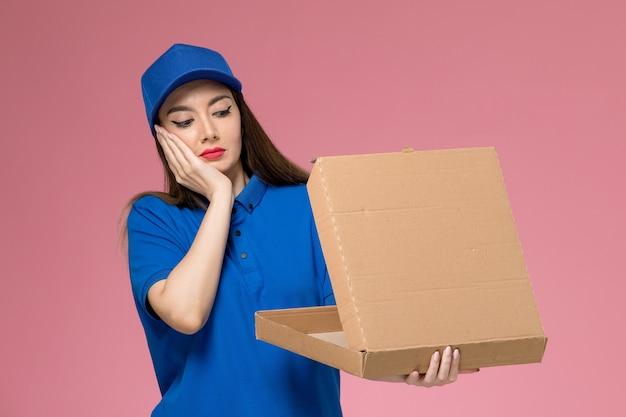 Vue de face jeune courrier en uniforme bleu et cape tenant une boîte de nourriture avec une expression confuse sur le mur rose