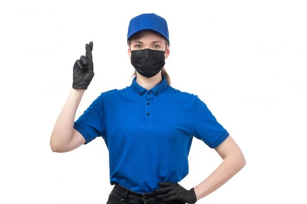 Une vue de face jeune courrier en uniforme bleu gants noirs et masque noir posant avec les doigts croisés