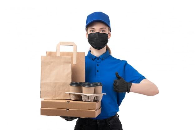 Une vue de face jeune courrier en uniforme bleu gants noirs et masque noir tenant des colis de livraison de nourriture