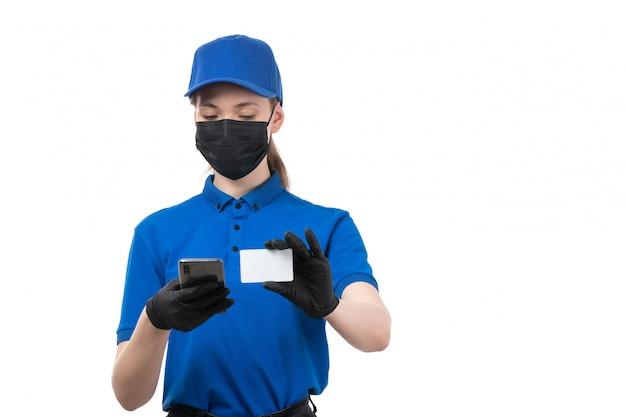 Une vue de face jeune courrier en uniforme bleu gants noirs et masque noir tenant téléphone et carte blanche