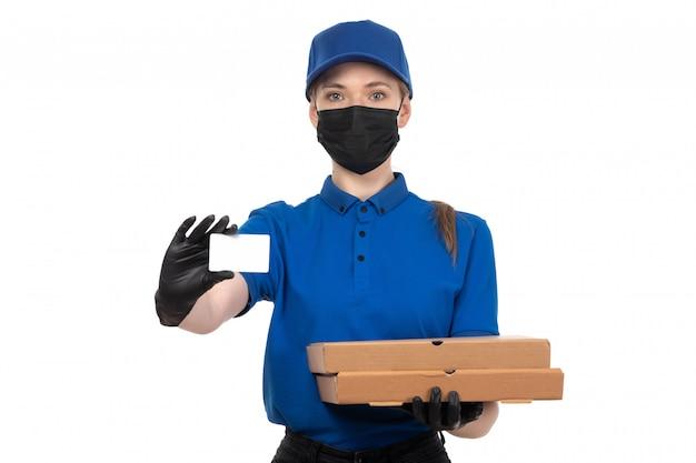 Une vue de face jeune courrier en uniforme bleu masque noir et gants tenant des colis de livraison de nourriture et carte blanche